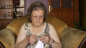 Old retired woman knitting in home