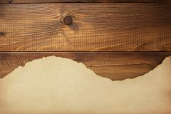 Old aged paper parchment at wooden background stock image