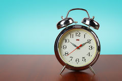 Old retro alarm clock on a wooden table Royalty Free Stock Photography