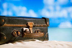 Old retro antique suitcase on beach. Sea and sky backgound Stock Photography