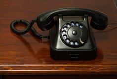 Old retro black telephone on desk Stock Photo