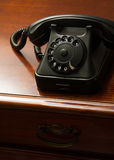 Old retro black telephone on desk Stock Photography