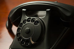 Old retro black telephone on desk Royalty Free Stock Images