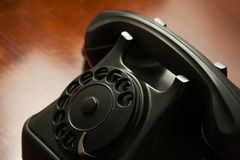 Old retro black telephone on desk Royalty Free Stock Photography