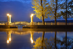 Old retro bridge and reflection over water. Royalty Free Stock Images
