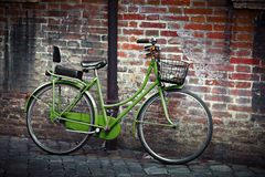 Old retro bycicle in Italy. Old green retro bycicle with basket against grunge wall in Ravenna, Italy Stock Photo