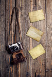 Old retro camera and blank instant photo frames on vintage wooden background Stock Photos