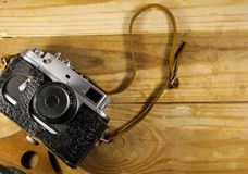 Old retro camera in leather case on wooden background Stock Image