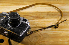 Old retro camera in leather case on wooden background Royalty Free Stock Photo