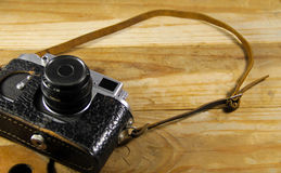 Old retro camera in leather case on wooden background Stock Photo