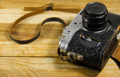 Old retro camera in leather case on wooden background Stock Photos