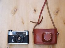 Old retro camera with leather case on wooden background Stock Photography