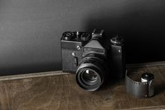 Old retro camera and 35 mm. Film in cartridge on a vintage background Royalty Free Stock Images
