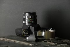 Old retro camera and 35 mm. Film in cartridge on a vintage background Stock Photos