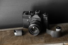 Old retro camera and 35 mm. Film in cartridge on a vintage background Royalty Free Stock Photo