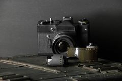 Old retro camera and 35 mm. Film in cartridge on a vintage background Royalty Free Stock Photos