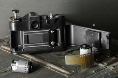 Old retro camera and 35 mm. Film in cartridge on a vintage background Royalty Free Stock Photography