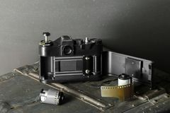 Old retro camera and 35 mm. Film in cartridge on a vintage background Stock Image