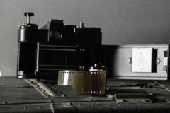 Old retro camera and 35 mm. Film in cartridge on a vintage background Stock Photography