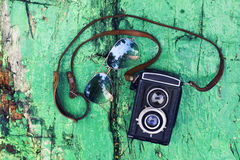 Old retro camera with sunglasses on vintage wooden background Royalty Free Stock Photo