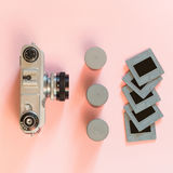 Old retro camera with three box for film and some slides on pink background. Concept royalty free stock photography