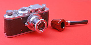 Old retro camera with tobacco pipe on vintage wooden board Royalty Free Stock Photos