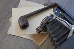 Old retro camera with tobacco pipe on wooden board Stock Images