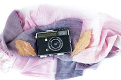 Old retro camera on vintage scarf with autumn leaves on white background . Stock Photos