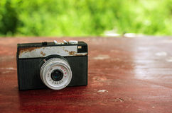 Old retro camera. On vintage wooden boards abstract green background Royalty Free Stock Image