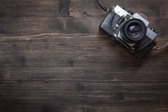 Old retro camera on wooden table background. Old retro camera on vintage wooden table background Royalty Free Stock Photo