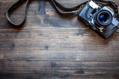 Old retro camera on wooden table background. Old retro camera on vintage wooden table background Royalty Free Stock Photography