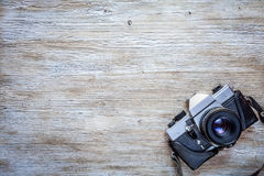 Old retro camera on wooden table background. Old retro camera on vintage wooden table background Royalty Free Stock Images