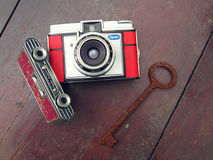 Old retro cameras and a rotten key. Udine, Italy - 16 June, 2016: two retro film cameras and a rotten key lying on a wooden table, a perfect vintage still life Royalty Free Stock Images