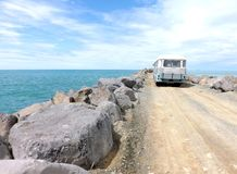 Old Retro Camper Bus. Parked by the sea on a road lined by rocks Stock Photography