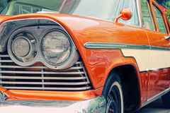 Old retro car on a show. Closeup of oldtimer car with orange colored paint on automobile show Stock Image