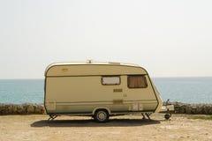 Retro caravan on the shore. Old retro caravan staying on a beautiful sea coast Royalty Free Stock Images