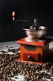 Old retro coffee grinder on wooden background with coffee beans Royalty Free Stock Photography