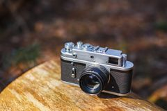 Old retro film camera in a sunny spring forest stock photo