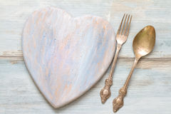 Old retro heart wooden cutting board and cutlery Royalty Free Stock Image