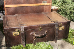 Old retro leather suitcases. Old closet locked retro vintage leather suitcases on stone paved surface closeup Stock Photo