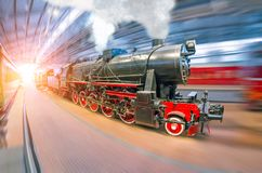 An old retro locomotive train railroad with steam and smoke clubs arrives at the passenger covered station under the roof. An old retro locomotive train royalty free stock photos