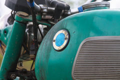 The old retro motorcycle - partial view of dirty tank with smudges of gasoline and  handlebar. The old retro motorcycle - partial view of dirty tank with smudges Royalty Free Stock Photography