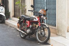 Old retro motorcycle stills ready to ride. Motorcycle is parking outside the shop.It has scratch all over but it`s still in good condition and ready to ride Royalty Free Stock Photo