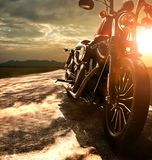 Old retro motorcycle traveling on country road against beautiful. Light of sunset sky Stock Photo