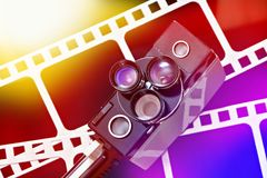 Old retro movie camera on background of perforation film Stock Images