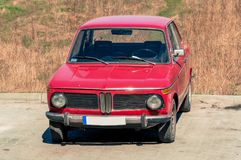 Old retro polish car in red standing in parking lot by field stock image