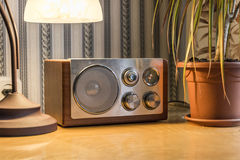 Old retro radio. Old radio with a lamp and a flower on and old wooden table Royalty Free Stock Image