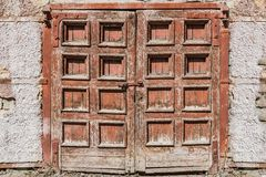 An old retro shabby wooden painted brown double door with a lock and a fragment of an old plastered wall with bare bricks stock photo