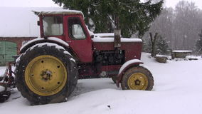 Old retro sovietic tractor in farm on snow and snowfall stock footage