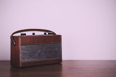 Old retro style radio on a wooden surface Vintage Retro Filter. Royalty Free Stock Photos